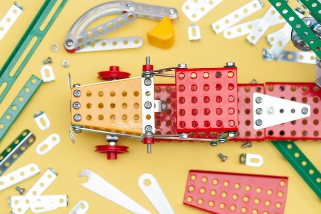 Металл, железный конструктор на желтом фоне. детали детского конструктора из металла для лепки.
