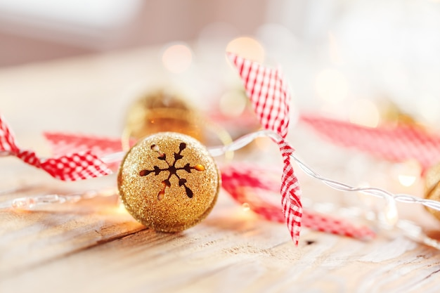 Metal jingle bells and christmas garland light on wooden background