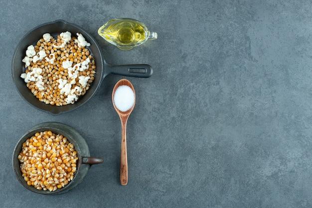 Brocca in metallo e padella piena di chicchi di mais, con un cucchiaio di sale e un bicchiere d'olio su fondo marmo. foto di alta qualità