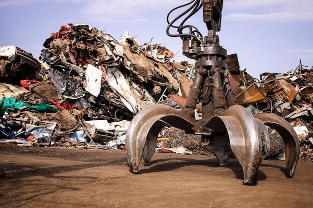 고철 재활용을 위한 발톱 부착 장치가 있는 유압식 리프팅 기계가 있는 금속 쓰레기 야드.