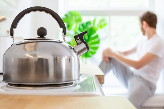 Metal kettle on electric stove. in the background, a young man sits on the windowsill.