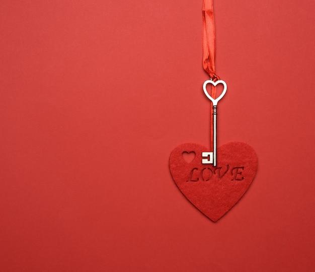 금속 키와 빨간색 느낌 된 마음은 빨간 리본, 빨간색 배경에 걸어