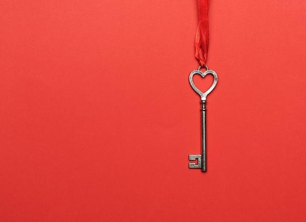 赤いリボン、赤い背景、コピースペースにぶら下がっている金属の鍵