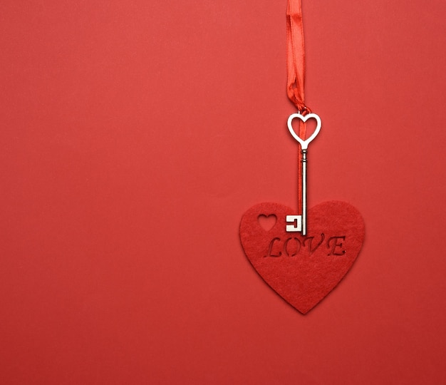 Metal key and red felt heart hang on red ribbon, red background