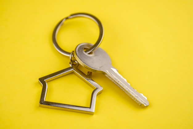 Metal keyring in the shape of a house with a key on a yellow.