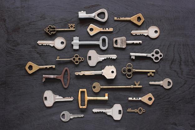 Metal keys on a black wooden background