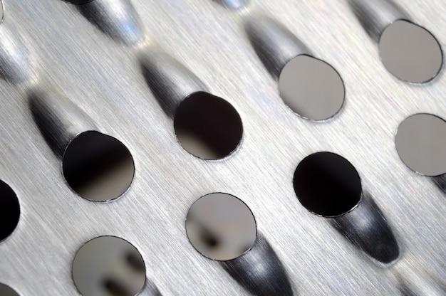 큰 구멍이있는 금속 주방 강판. 매크로.