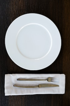 Metal knife and fork on a light napkin. appliances for food. next to the empty plate.