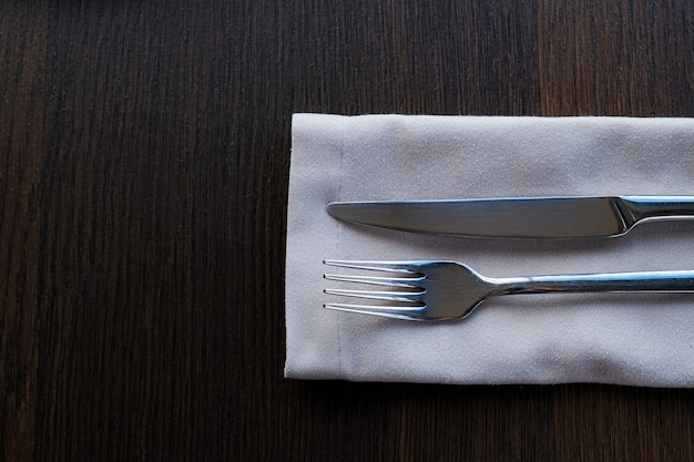 A metal knife and fork on a napkin on the table. clean cutlery for food. table setting.