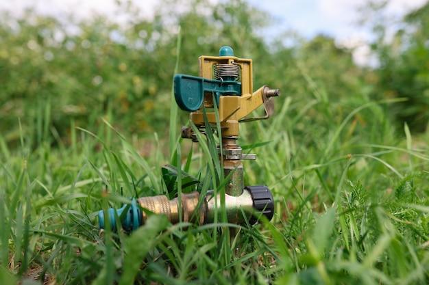 Металлическая система полива газонов на зеленой траве фон крупным планом концепция ухода за садом