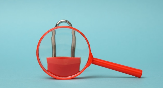 Metal lock stands on a red plastic magnifying glass on a blue background. data protection concept, personal information