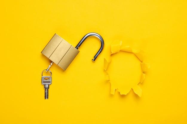 노란색에 고립 된 열쇠로 금속 자물쇠