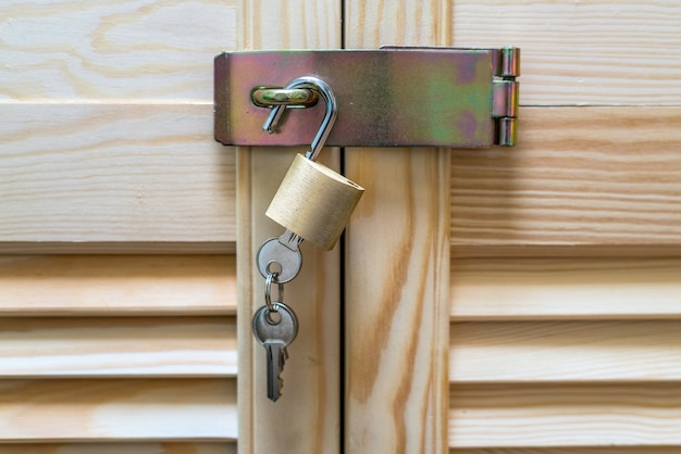Metal lock with keys hanging on modern wooden cabinet with strips.