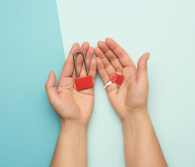 女性の手に鍵が付いた金属製の錠