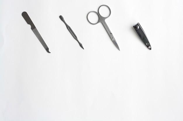 Металлический маникюрный набор, пинцет, ножницы, пилка и шпатель на белом фоне, плоская планировка, копировальное пространство