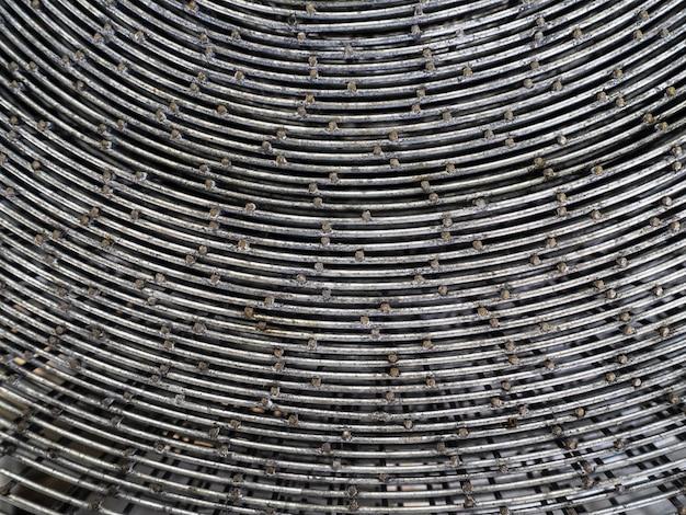 ロール状にねじれた金属メッシュ。フェンス取り付け用の鉄メッシュ。ねじれた格子の平面図