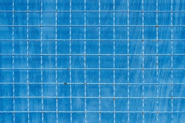 파란색 페인트 배경에 사각형 셀이 있는 금속 메쉬