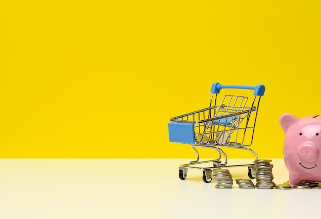 Metal miniature shopping cart with change and pink piggy bank on a white table, yellow background. concept of saving budget, discounts