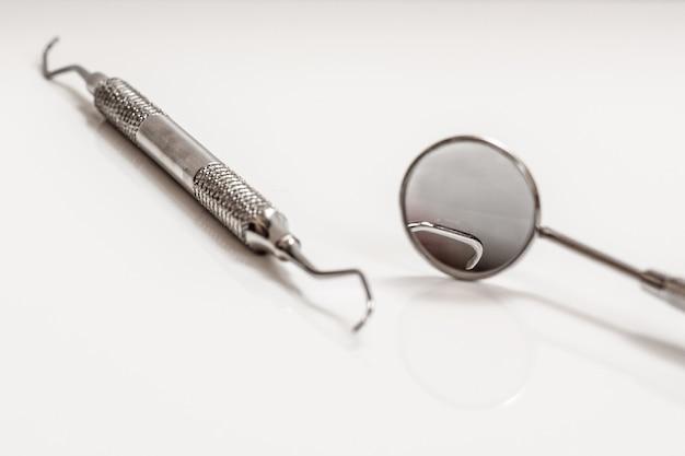금속 거울과 프로브. 검은 배경에 치과 치료를 위한 치과 도구입니다. 의료 도구. 클로즈업 보기입니다. 필드의 얕은 깊이. 금속 거울에 초점을 맞춥니다.