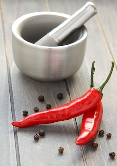 Metal mortar and pestle with pepper on wooden background