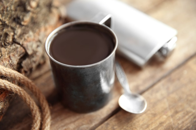 Metal mug of coffee with flask, spoon and rope on wooden