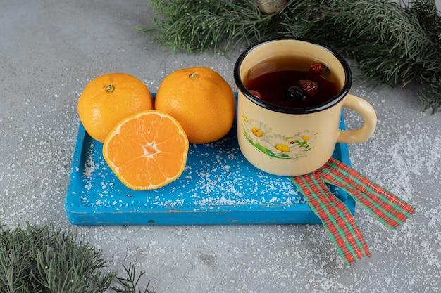 Tazza di metallo di tè alla rosa canina su un piatto con arance in un allestimento festivo su una superficie di marmo