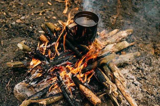 Metal mug heats up on bonfire