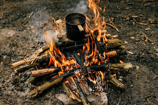 금속 머그잔이 모닥불에 가열됩니다.