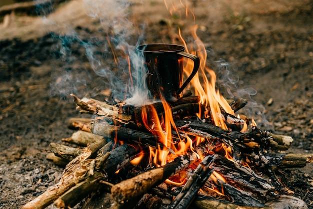 금속 머그잔이 모닥불에 가열됩니다. 프리미엄 사진