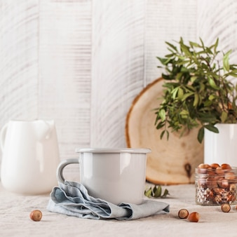 A metal mug on a linen tablecloth a white jug of milk on the back still life in rustic style copy space