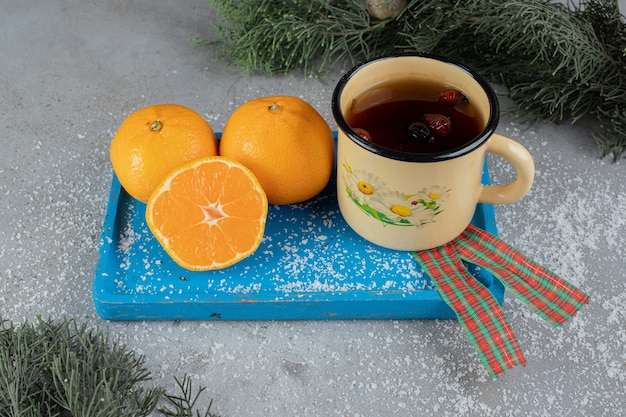대리석 표면에 축제 분위기로 오렌지와 함께 플래터에 개 장미 차의 금속 머그