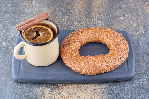 말린 레몬 슬라이스 계피 스틱과 대리석 표면에 보드에 베이글과 차의 금속 머그잔