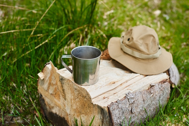 Metal mug and tourist hat with fields lie on a log in the forest