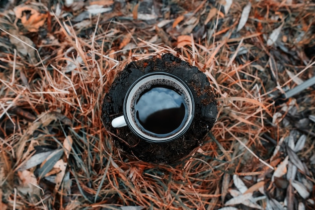秋の森の木の切り株の上に、温かい飲み物を入れた金属製のマグカップが立っています。空がカップに映る