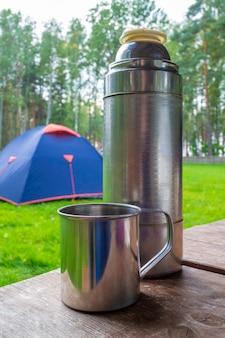 나무 테이블에 보온병과 금속 찻잔입니다. 배경에서 파란색 여행용 텐트입니다.