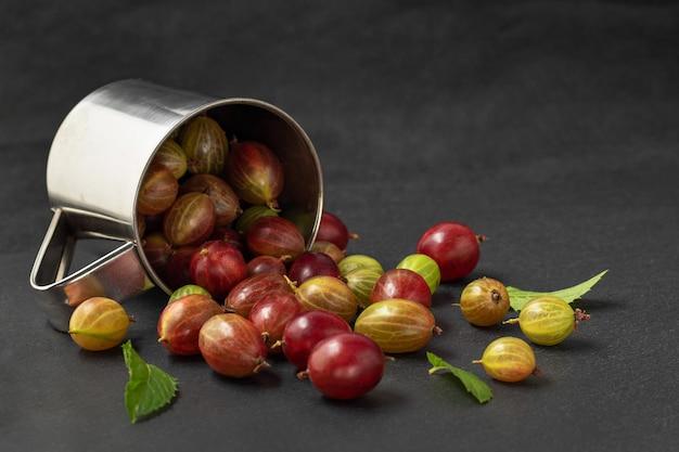 Metal mug and yummy gooseberries on grey table, copy space