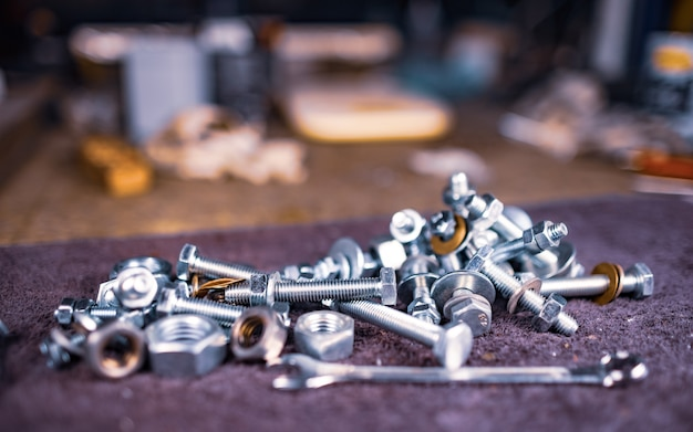 조립자의 작업 테이블에 금속 너트 볼트와 렌치가 놓여 있습니다.