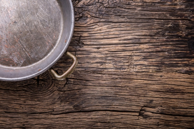 오크 식탁에 있는 금속 오래된 복고풍 빈 팬. 평면도.