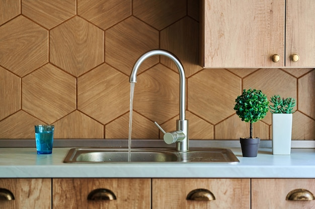 Metal open tap faucet with running water and sink in the kitchen interior