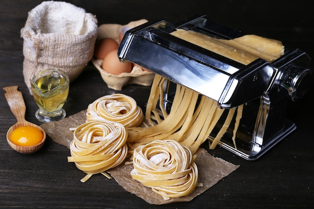 Metal pasta maker machine and ingredients for pasta on wooden table