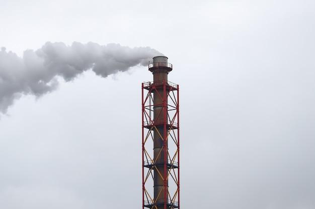 灰色の空を背景に白い煙が出る金属パイプ