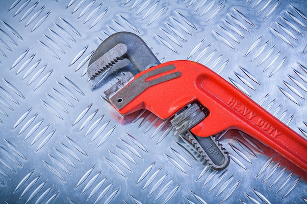 Metal pipe wrench on fluted metallic sheet construction concept