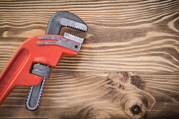 Metal pipe wrench on vintage wooden board copy space construction concept