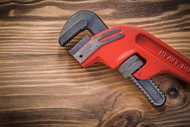 Metal pipe wrench on vintage wooden board directly above