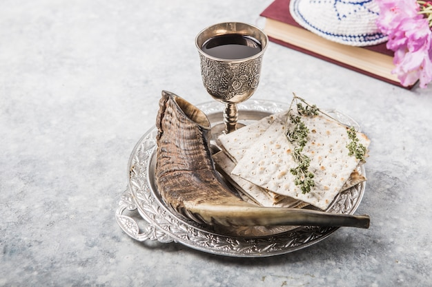 Metal plate with matzah kiddush cup, shofar horn  on a light  background presented as a passover seder feast or meal with copy space. jewish traditional objects, yarmulke, tallit, prayer book