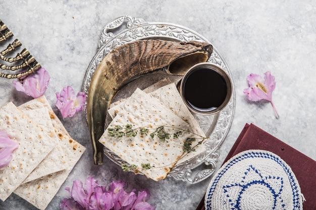 パッツァーセダーのごちそうまたはコピースペース付きの食事として提示された、明るい背景のマッツァーキダッシュカップ、ショファルホーンの金属板。ユダヤの伝統的なオブジェクト、yarmulke、tallit、祈りの本