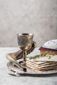 明るい背景にマツァーまたはマツァー、キッダッシュカップ、ショファルの角が付いた金属板。過越祭のセダーのごちそうまたはコピースペース付きの食事。ユダヤの伝統的なオブジェクト、yarmulke、tallit、祈りの本