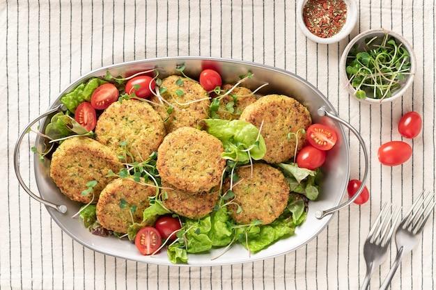 Металлическое блюдо с веганскими гамбургерами из киноа и салатом на полосатой скатерти