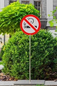 Металлический столб с табличкой для некурящих в общественном месте.