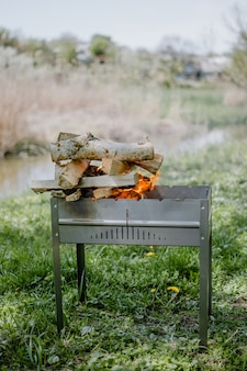 Metal portable barbecue with burning firewood and red flames